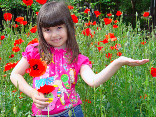 Girl with brown eyes on the field of red poppies.