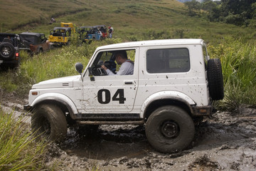 A white jeep splattered and caked with mud