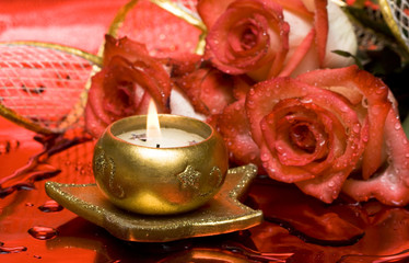 golden candle with red roses