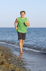 A  happy 44 year old man jogging along beach.