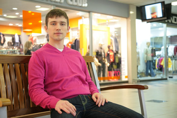 young man sits on bench in mall