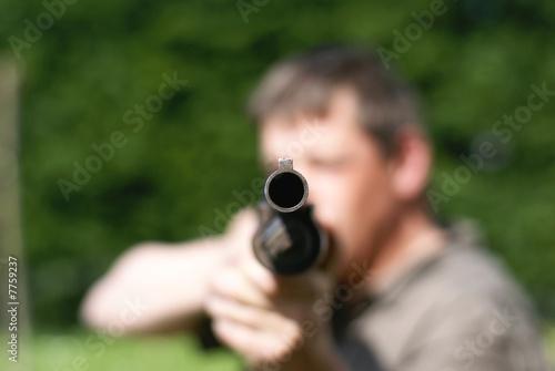 homme menaçant armé d'un fusil à pompe