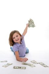 Pretty little girl holding a handful of American bills.