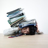 Businessman's head crunched by folders