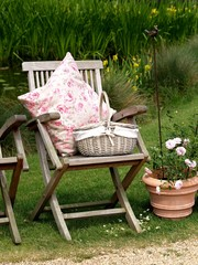 Kissen und Korb auf einem Teakholz Stuhl