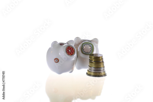 Two piggybanks and coins in white
