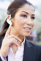 Businesswoman using bluetooth earpiece