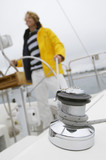 Young man on yacht in sea, focus on crank with rope