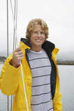 Young man standing on yacht, portrait