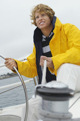Young man standing at yacht helm