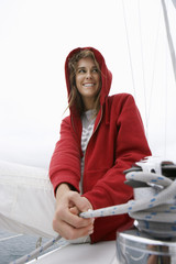 Young woman holding rope on yacht