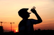 Biker drinking mineral water against sunset