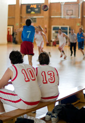 Basketball amateur. Two players waiting in bench