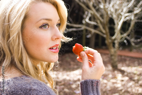 Beautiful young woman eating a strawberry in the park