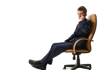 Businessman sitting on an armchair with cell phone.