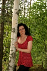 Happy young woman in birch wood