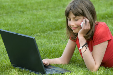 Teenager working at computer on the grass
