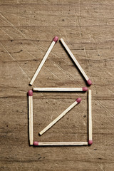 Matches on wooden surface forming a house shape.