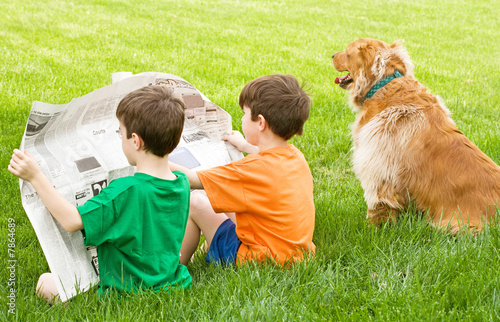 Leinwandbild Motiv Two Boys Reading the Newspaper