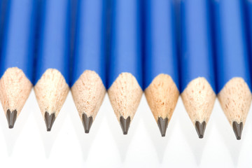 Sharp blue pencils in a row on a shiny reflecting surface