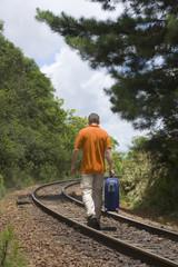 Mann geht auf Bahnschienen