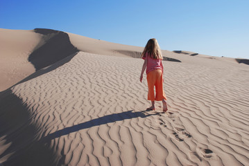 Young Girl Walking Wandering on Sand Dunes