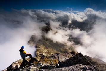 Man on the summit watching beautiful clouds