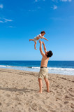 Father plays with his daughter on the summer beach