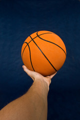 Basketball in men's hand against a black background