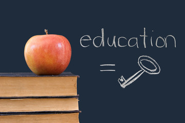 education = key - written on blackboard with apple, books