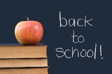 back to school written on chalkboard wiith apple, books