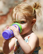 This two-year-old gazes skeptically over her sippy cup