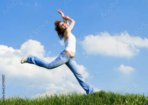 happy young woman jumping in green grass