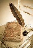 Old book, quill and bottle of black ink on old wooden chair