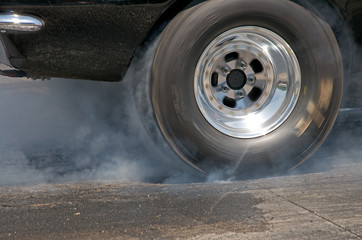Smoke from the tires of a black racer