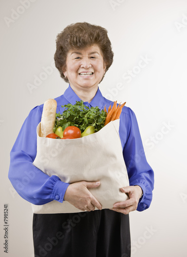 Portrait of a senior woman holding bag of groceries