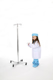 Young child dressed in medical scrubs next to an IV stand