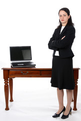 Business woman standing next to an open laptop on a desk.