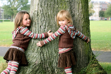 Sisters hugging a tree