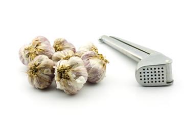 Raw garlic and garlic press, isolated