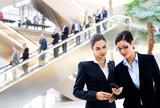 Businesswomen looking at cellphone poster