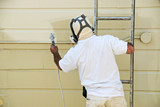 A man on a ladder uses paint spray gun