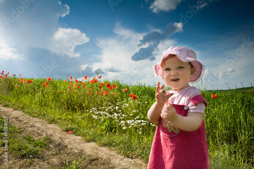canvas print picture Baby-girl on a lane amongst a field