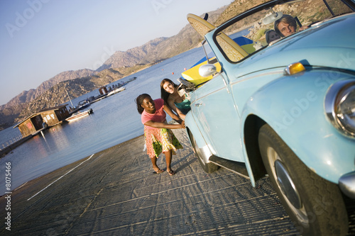 Two teenage girls (17-19) pushing blue car, lake in background, teenage boy steering (tilt)