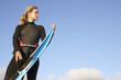 Woman standing on beach in wetsuit, holding surfboard, low angle view
