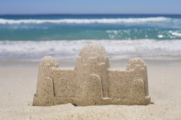 Sandcastle on sandy beach, sea in background