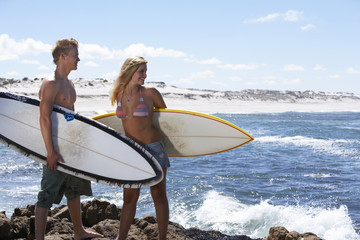 South Africa, young couple standing on rock beside sea, carrying surfboards under arm, smiling