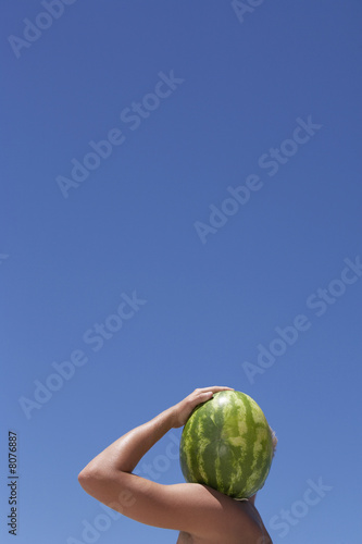 Man carrying watermelon on shoulder, face obscured, profile, clear blue sky in background