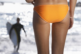 Young woman in orange bikini watching surfer in sea, rear view, mid-section, focus on foreground