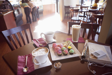 Iced coffee, latte, black coffee and cakes on serving dish beside MP3 player and publications on cafe table, elevated view (tilt, still life)